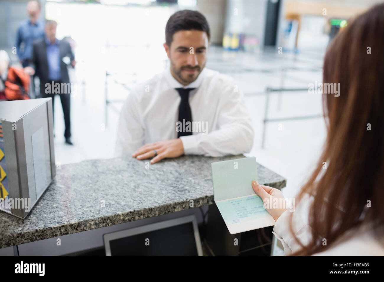 Airline check-in attendant checking passport of passenger - Stock Image