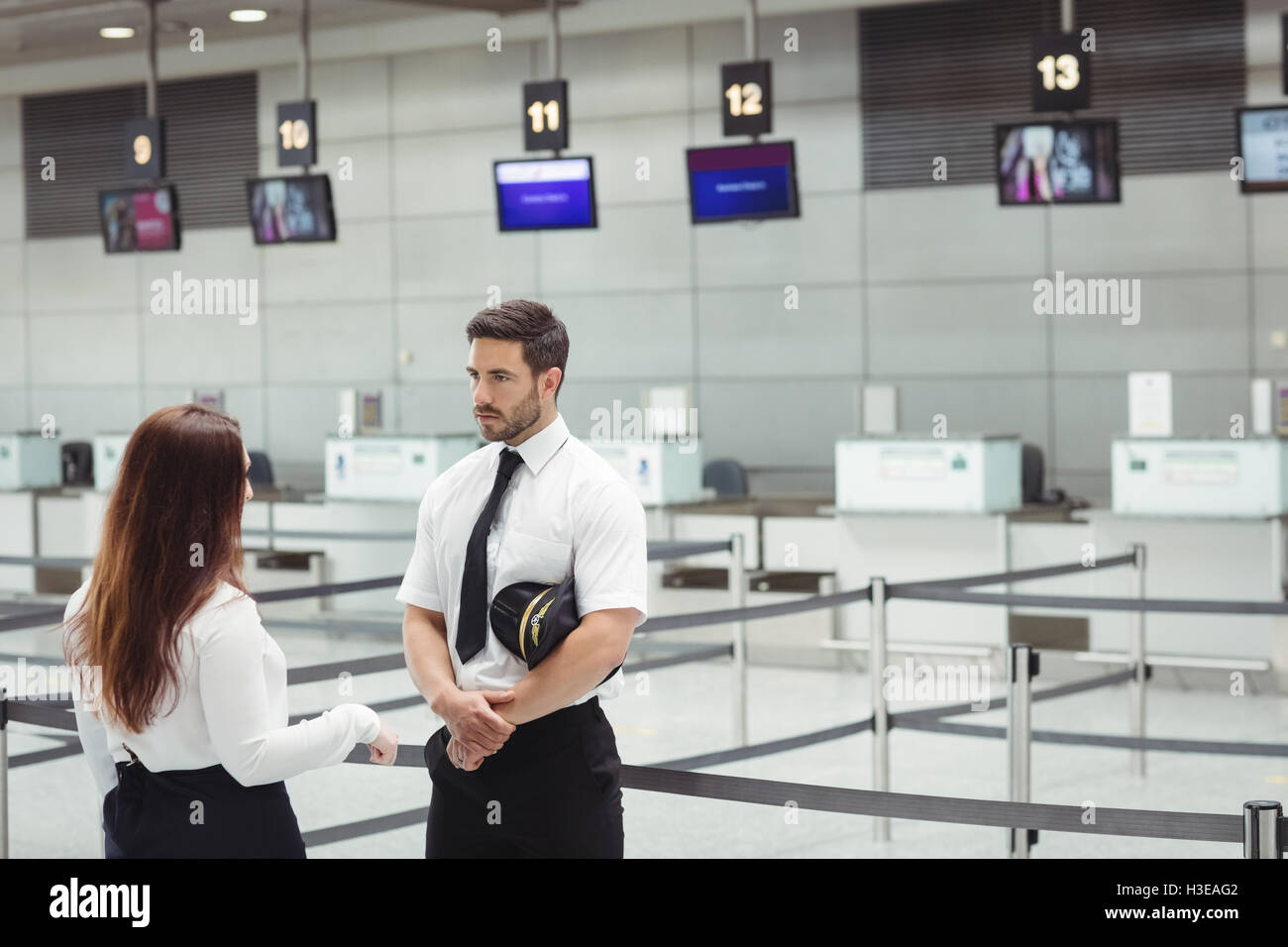Pilot and flight attendant interacting with each other - Stock Image