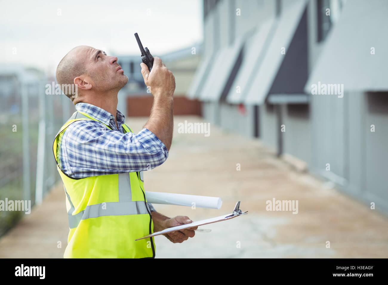 Construction worker talking on walkie-talkie - Stock Image