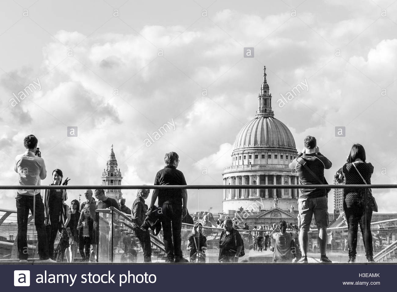 Black and white image of sightseers looking at and photographing St. Paul's Cathedral from the South side of - Stock Image