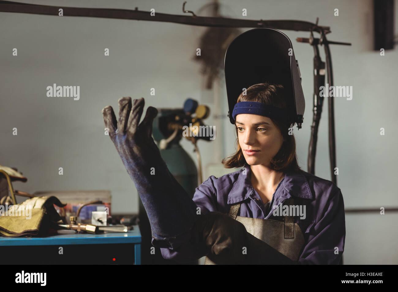 Female welder wearing glove - Stock Image