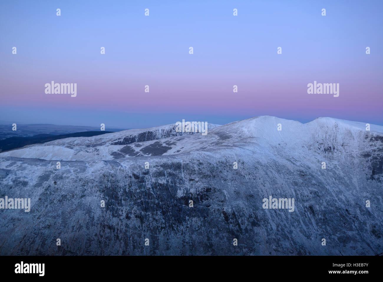 Dawn, the twin peaks of Saddle Yoke (left) and Under Saddle Yoke (right), with Nether Coomb Craig (behind left) - Stock Image