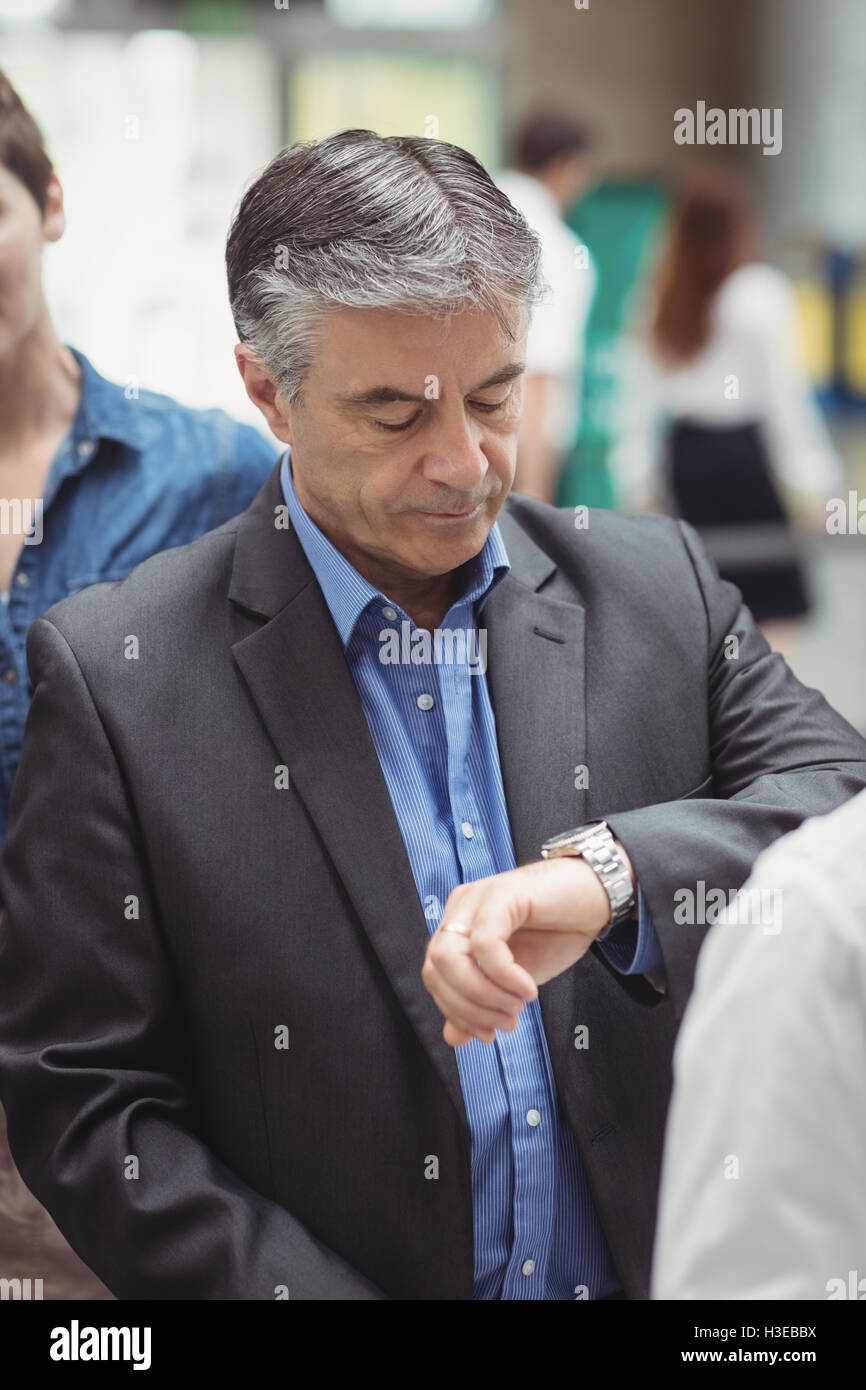 Business man checking time while standing in queue Stock Photo