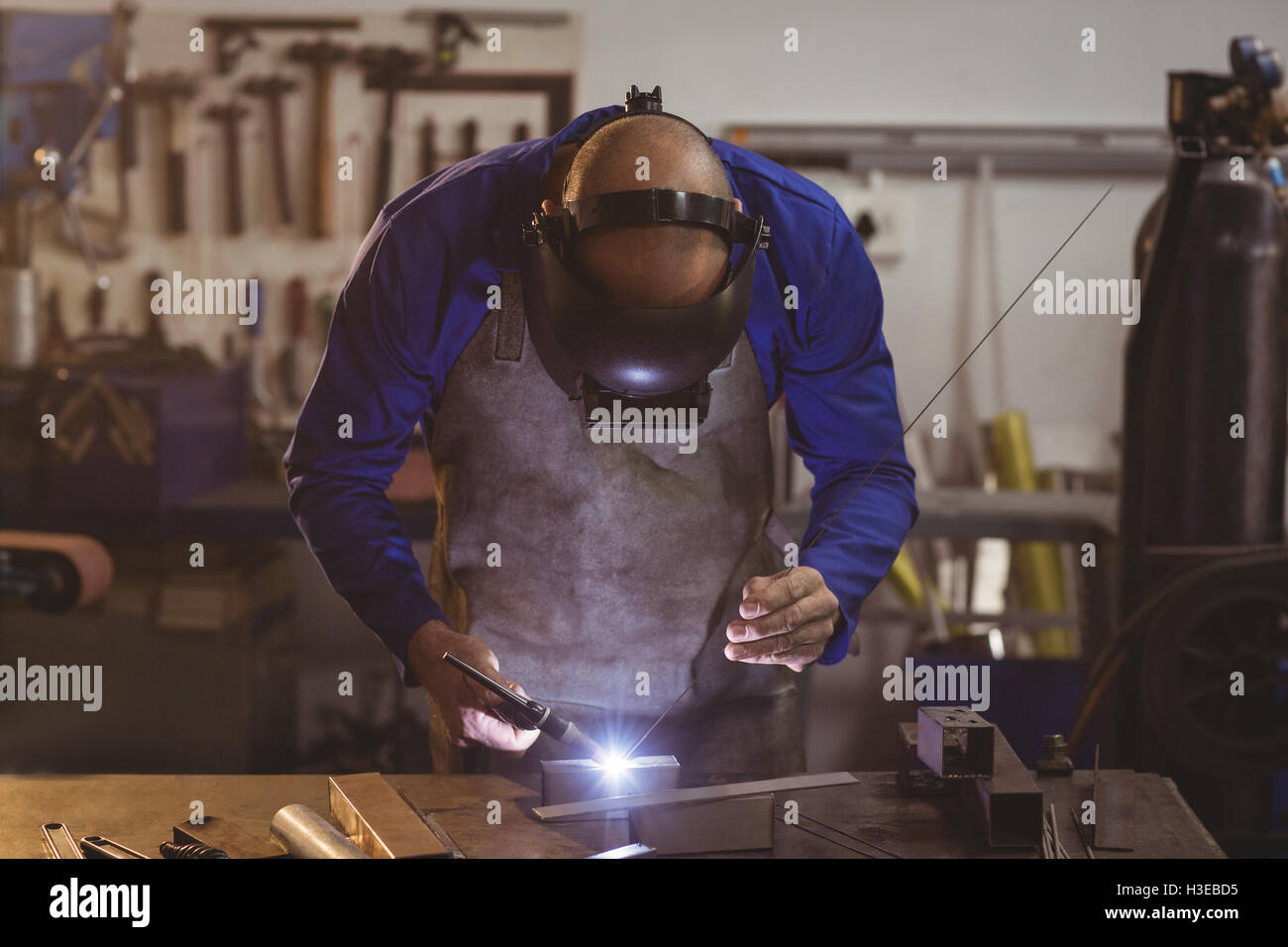 Male welder working on a piece of metal - Stock Image