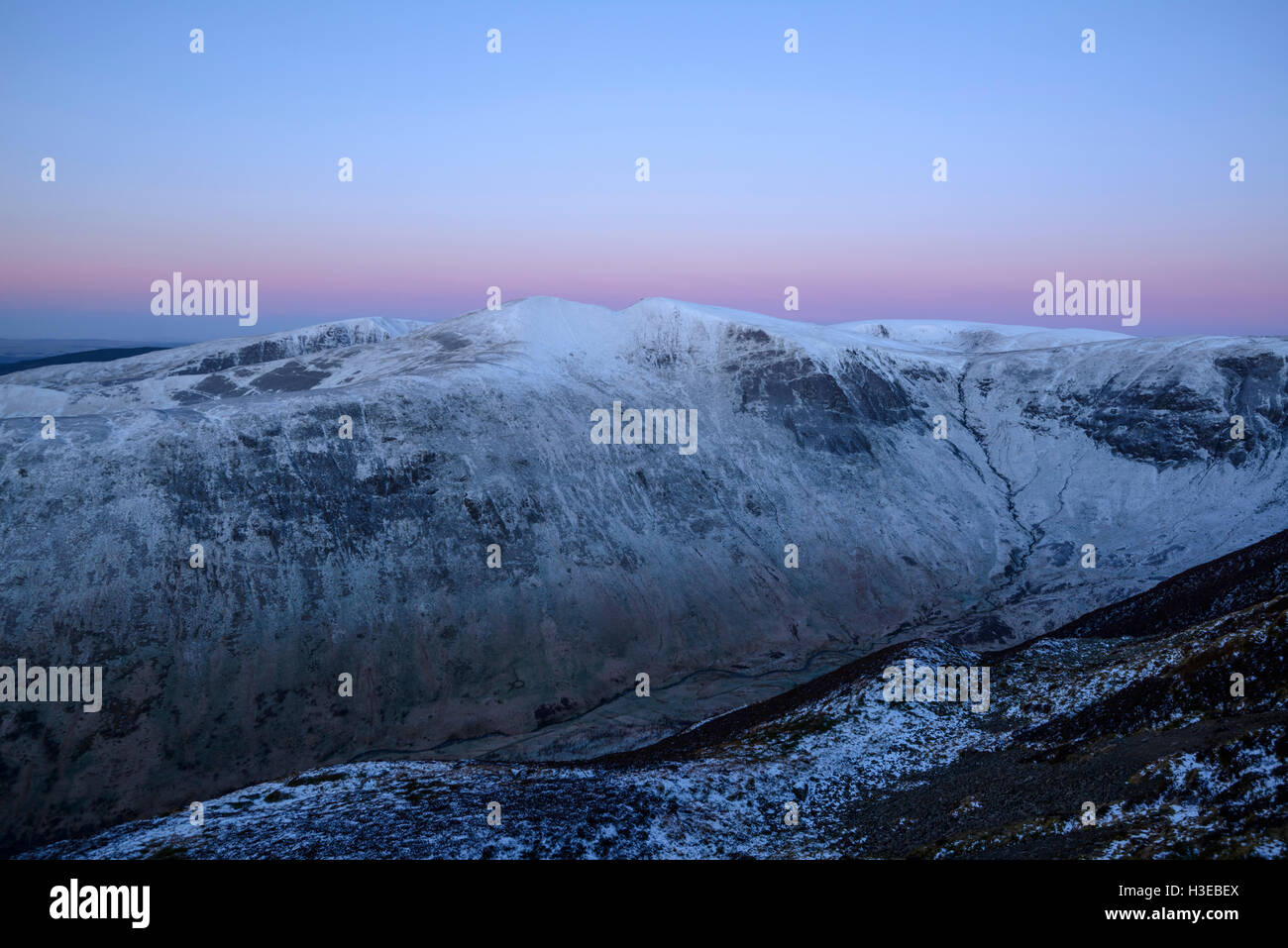 Dawn, the twin peaks of Saddle Yoke (left) and Under Saddle Yoke (right), with Hart Fell (behind right) and Nether - Stock Image
