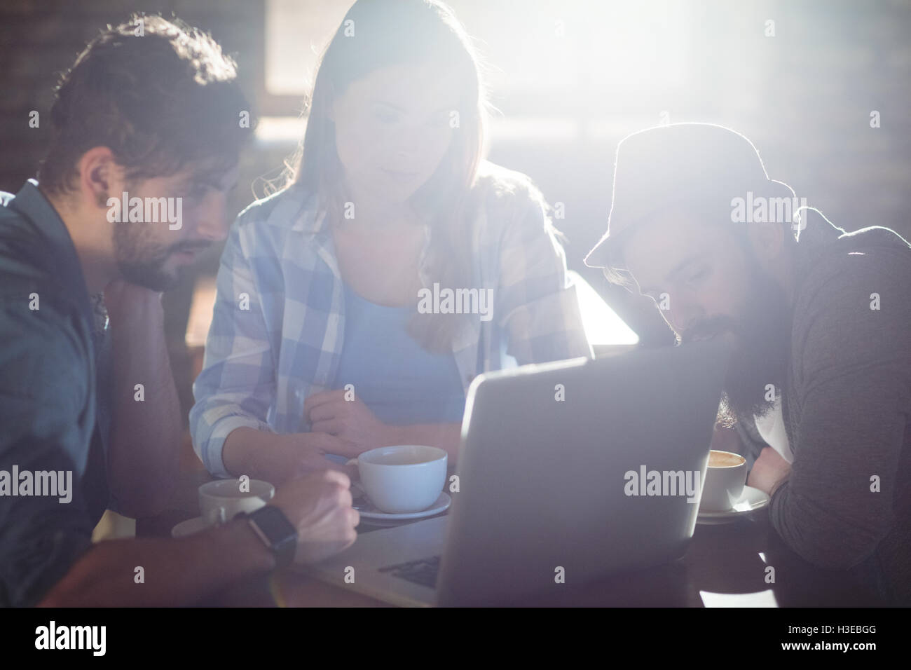 Friends using laptop at cafe - Stock Image