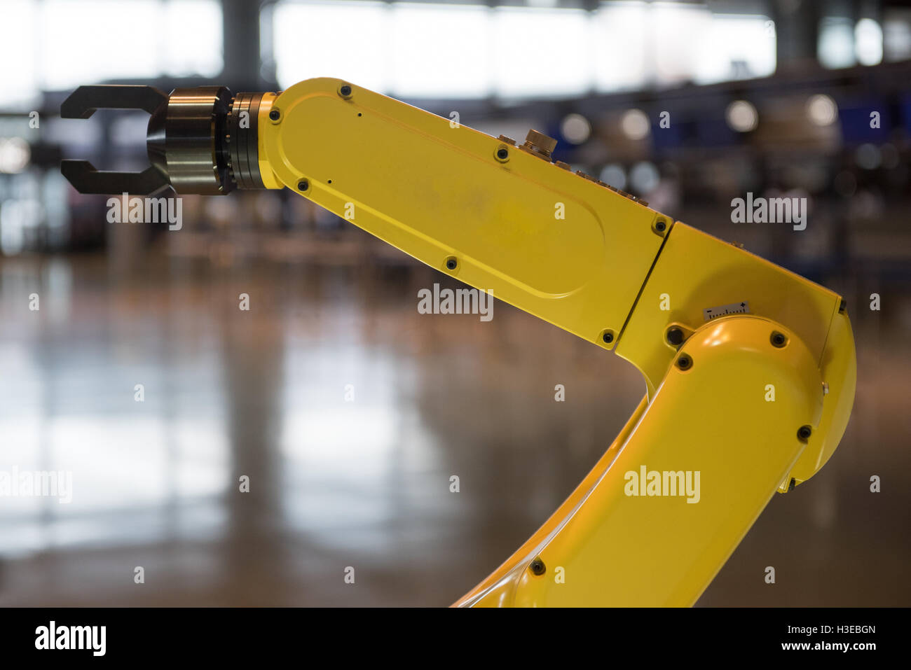 A yellow robotic arm isolated on a blurry background - Stock Image