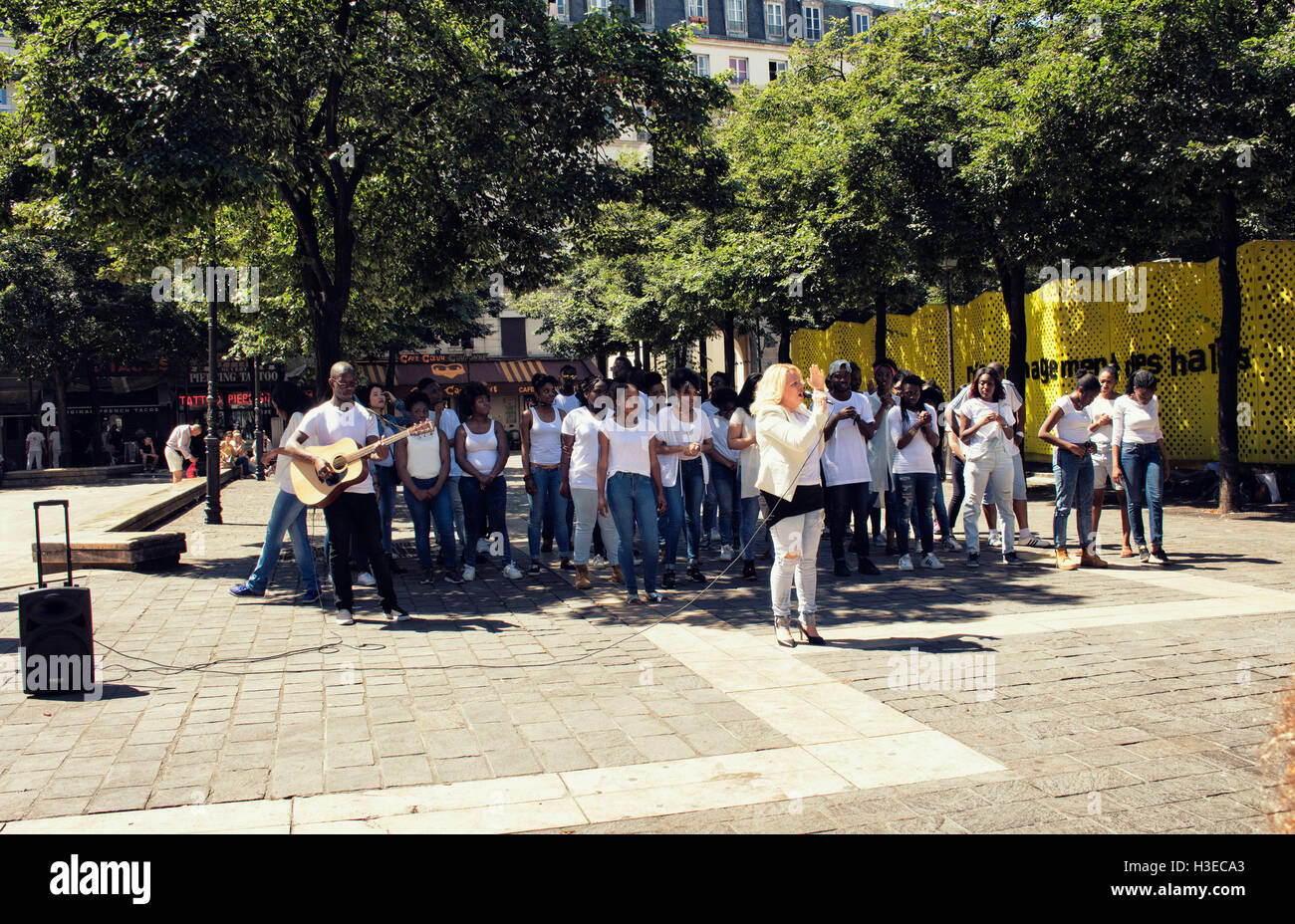 Middle age woman sings with a chorus of young African French teenagers near Les Halles station in Paris. - Stock Image