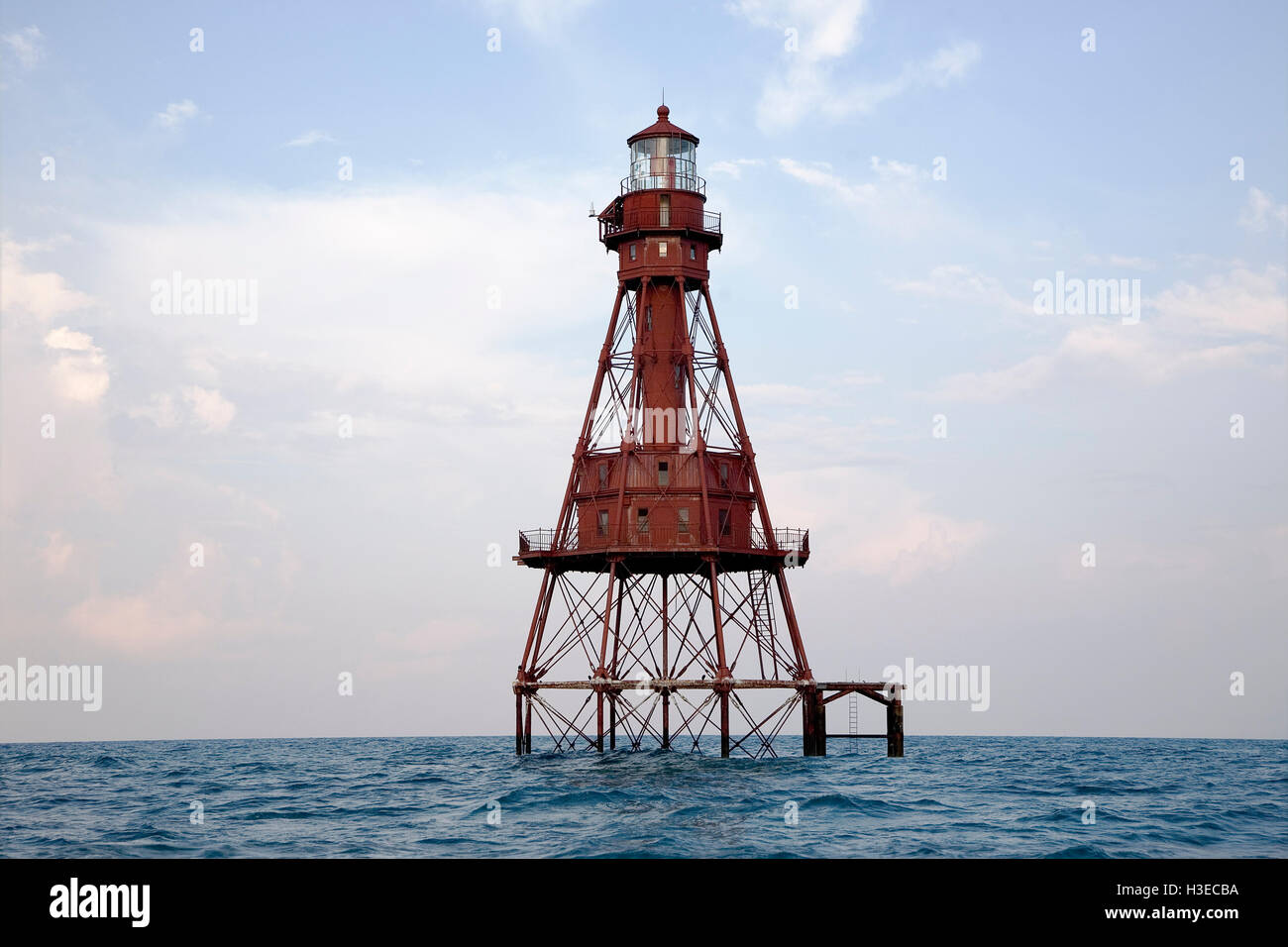 Florida's American Shoal Lighthouse with its iron screw-pile skeletal tower showing off its bright red color - Stock Image