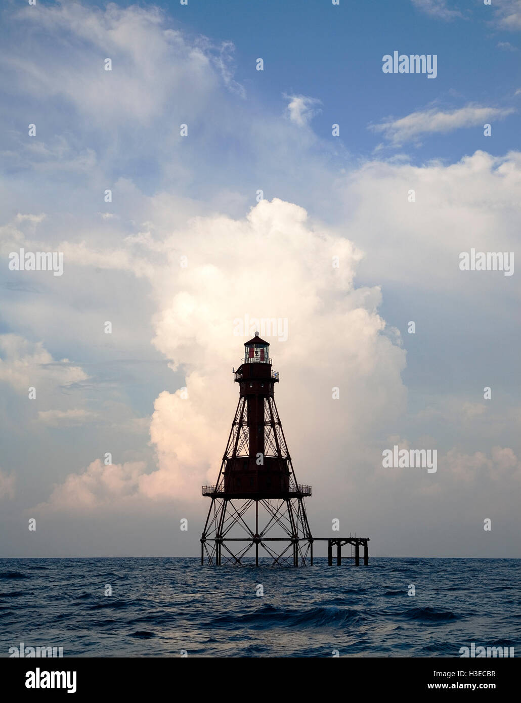 One of Florida's 6 Reef Lights the skeletal tower of American Shoal is picture at dawn with summer rain clouds - Stock Image