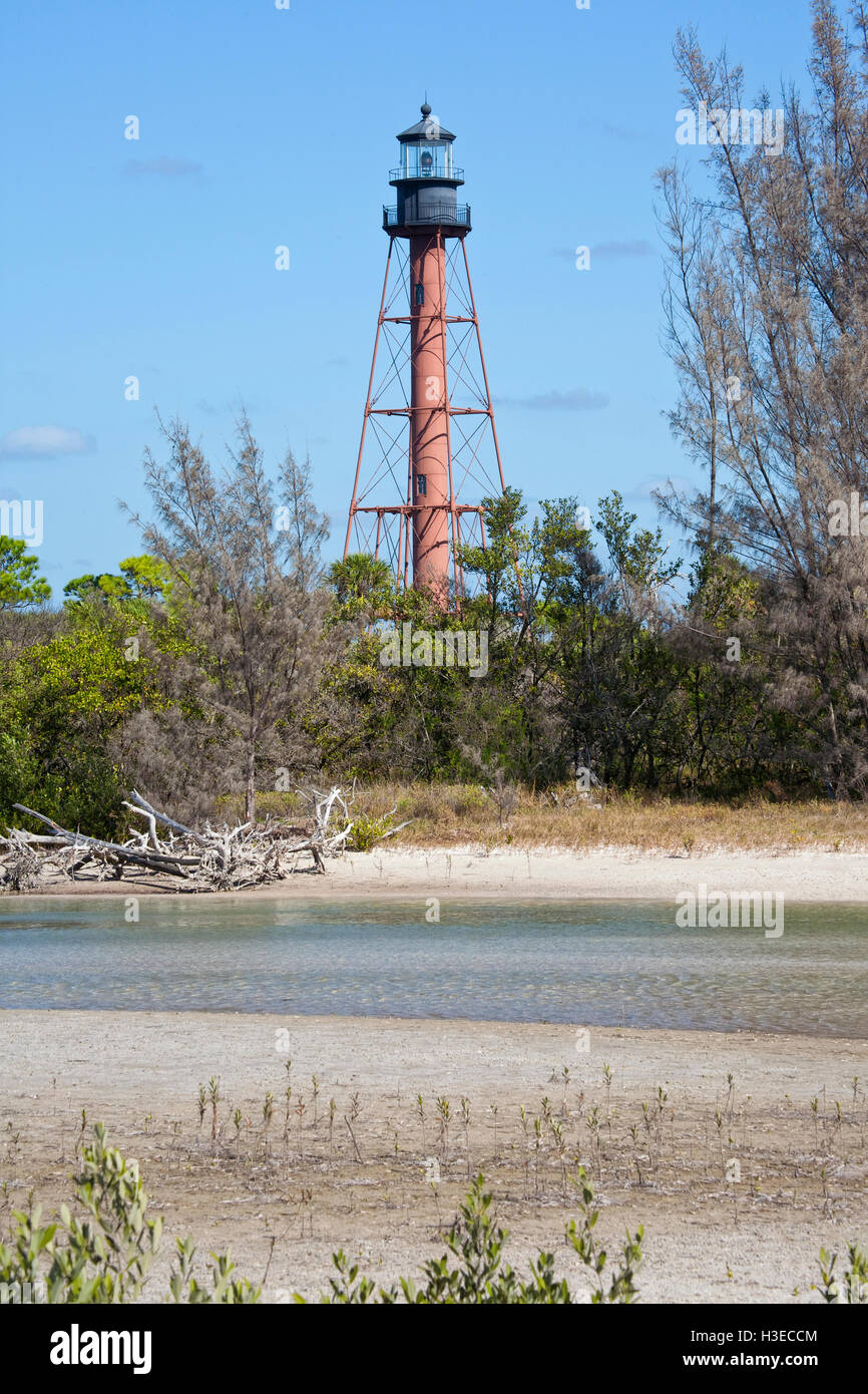 The brown skeletal tower of Anclote Key Lighthouse stand against a blue sky with a stream water running through. - Stock Image