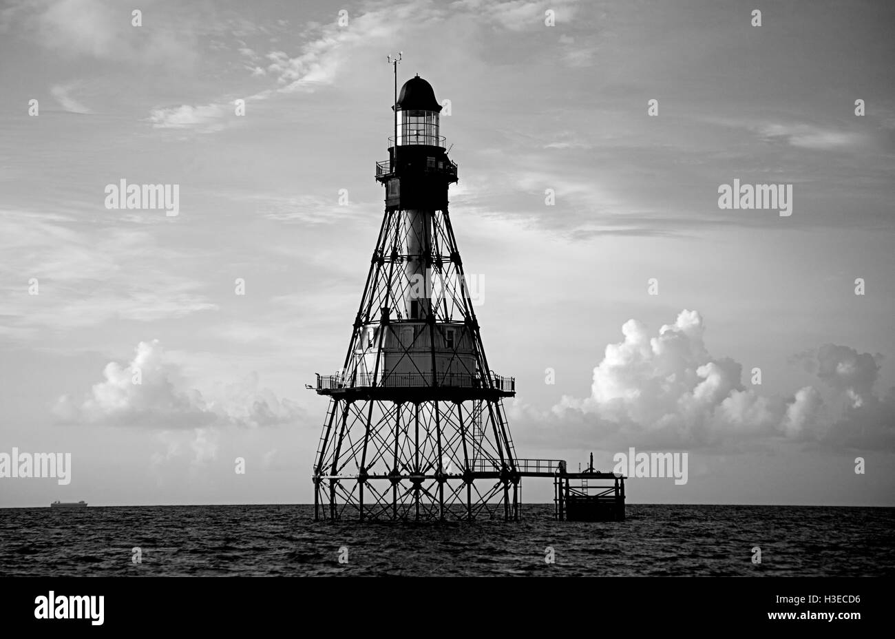 On a serene calm morning,Florida's Fowey Rocks Lighthouse greets the early light of day in this black and white - Stock Image