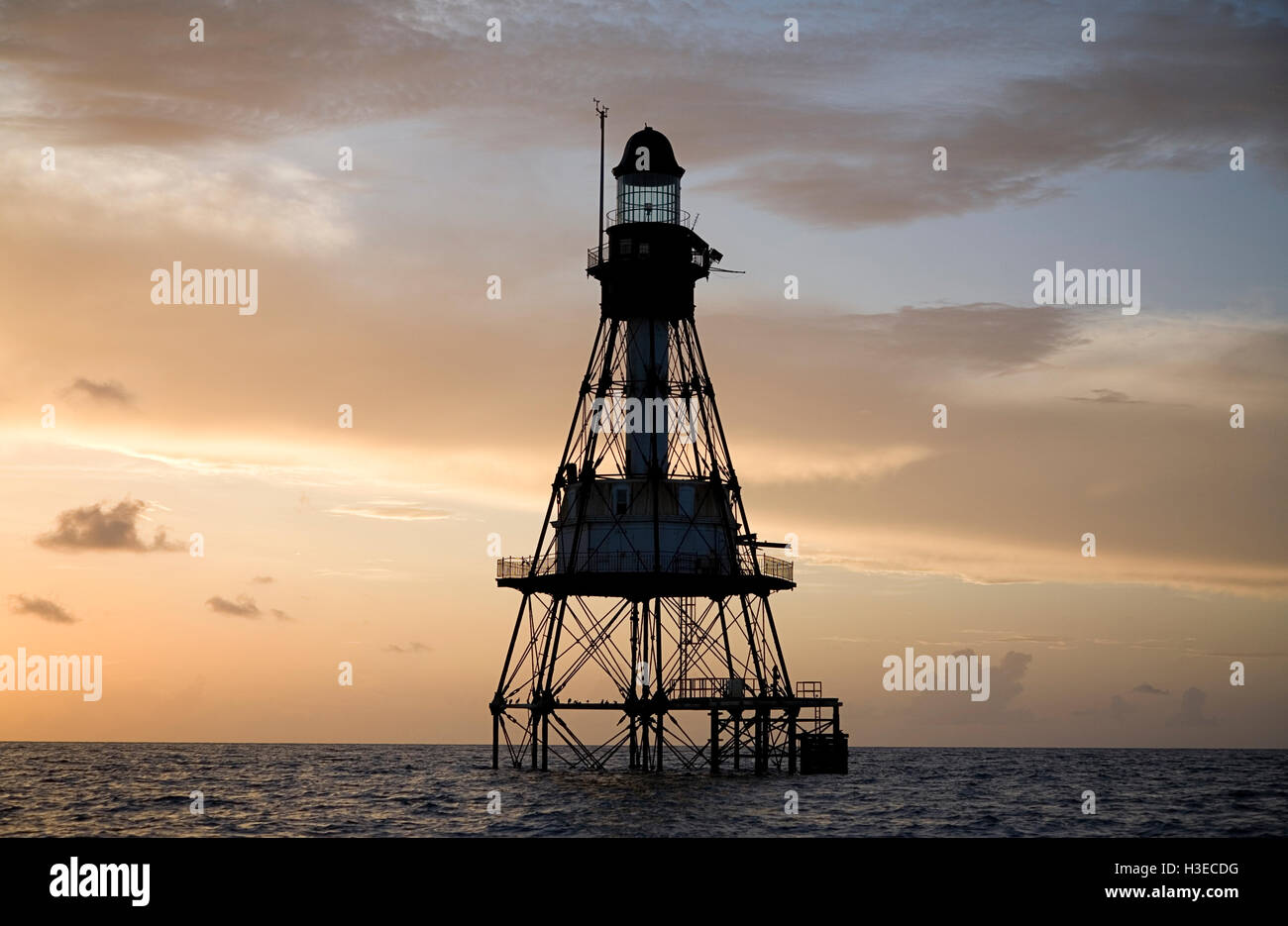 Fowey Rocks Lighthouse, one of Florida's 6 reef lights, is silhouetted against the peach-colored skies of a - Stock Image