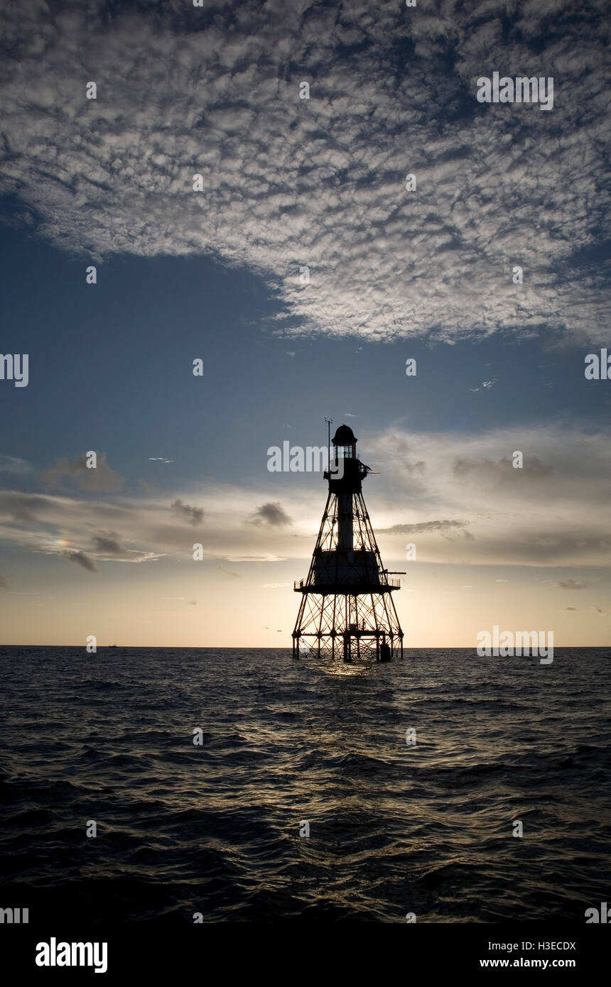 Fowey Rocks Lighthouse is silhouetted against the rising sun with fleecy clouds above and calm seas. - Stock Image