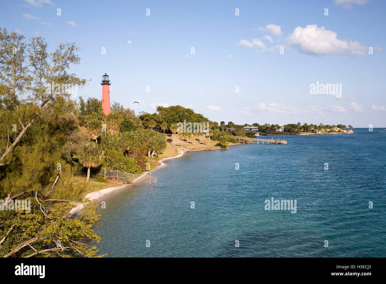 View of the Jupiter Inlet coast line from the Jupiter Inlet Bridge with the brick orange tower of Jupiter Lighthouse - Stock Image