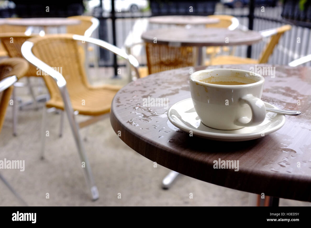 An empty coffee cup on a wet cafe table in Montreal. - Stock Image