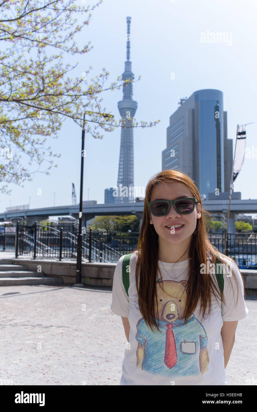Asian girl standing in front of view of sumida river and famous building in sumida area.Japan - Stock Image