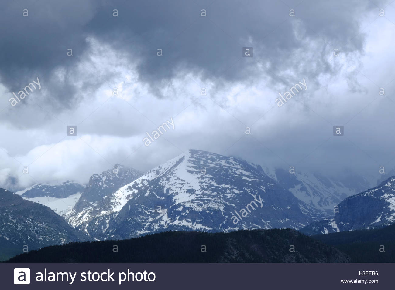 Snow covered mountain peaks reach the clouds in Rocky Mountain National Park, Colorado. - Stock Image