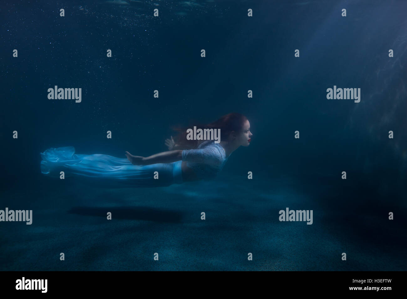 Woman as the mermaid swims under water, she in a white dress. - Stock Image