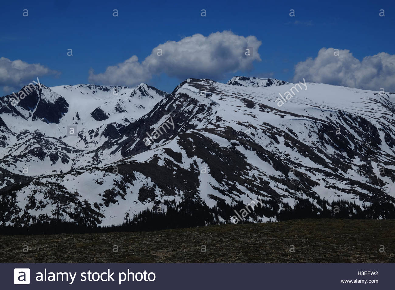 Patches of snow cover a mountain peak in Rocky Mountain National Park, Colorado. - Stock Image