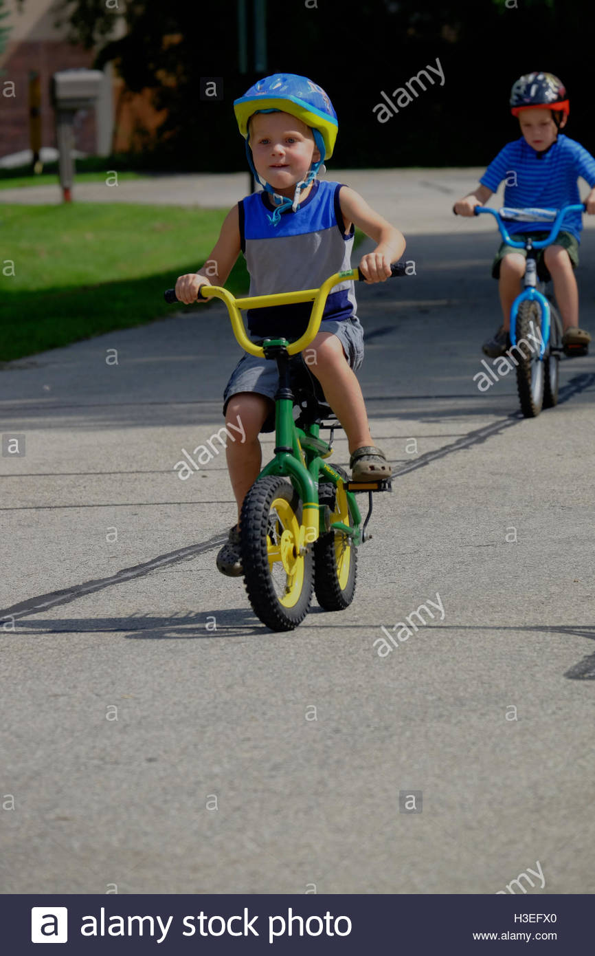 Two brothers riding two wheeled bikes on a street in New Berlin, Wisconsin. - Stock Image