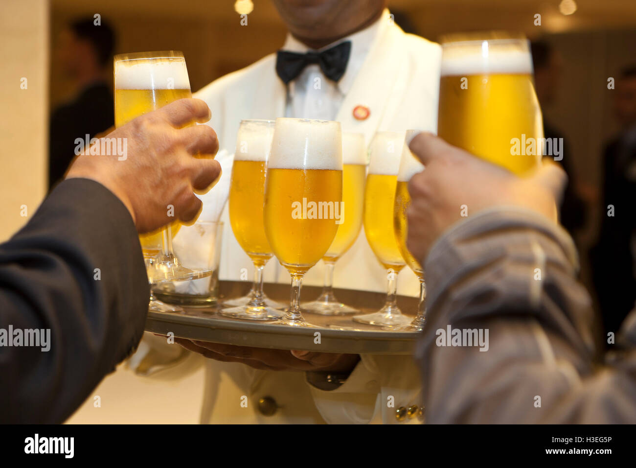 Happy hour, waiter serving beer to business people at office party. - Stock Image