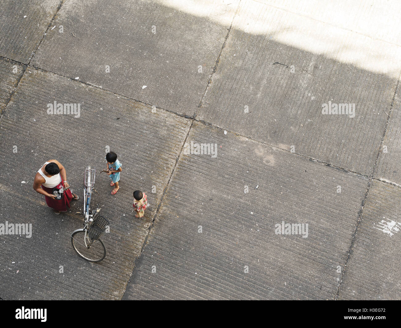 A father and his children replace their bicycle seat in Yangon, Myanmar (Burma) - Stock Image