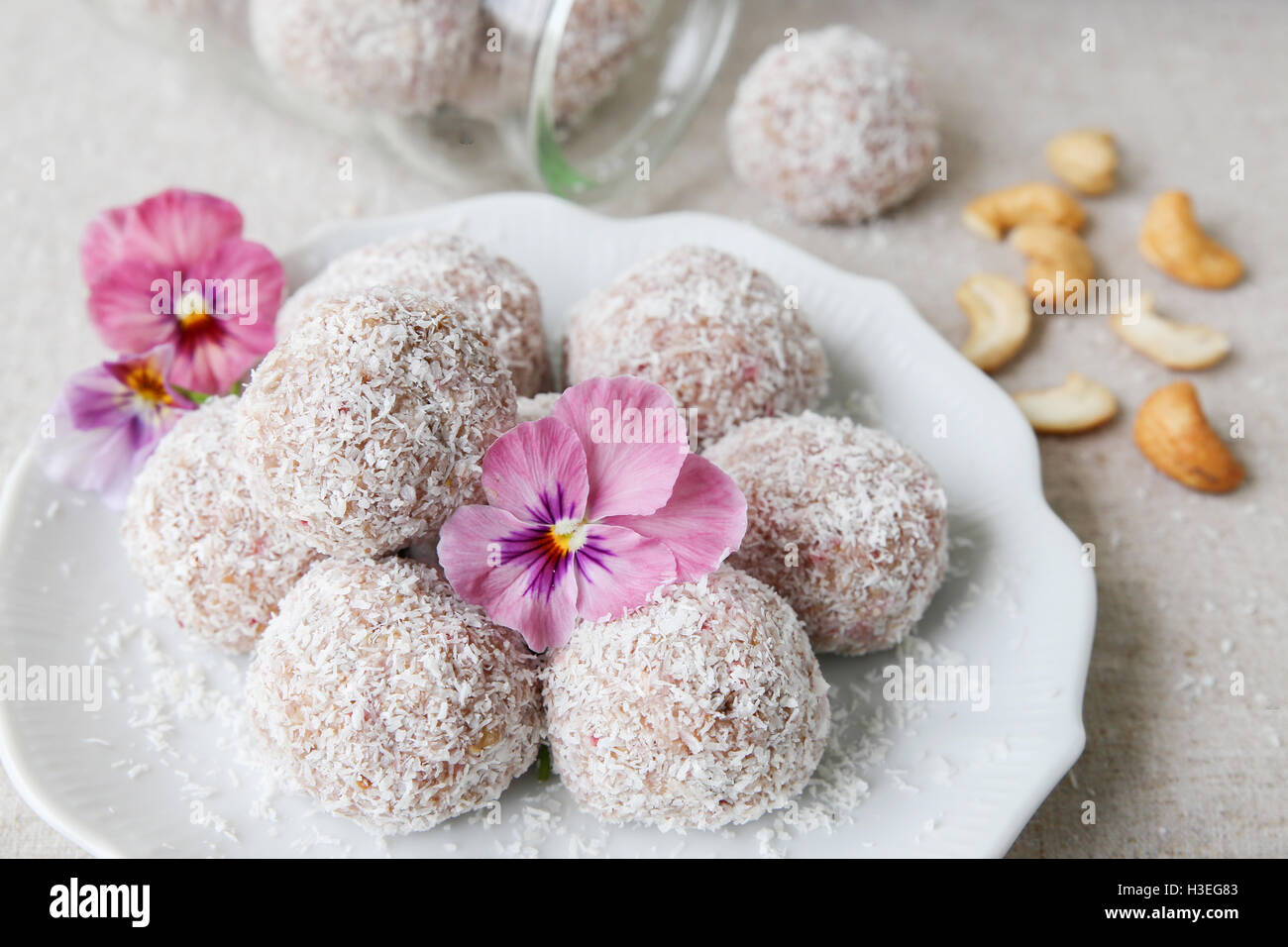 Homemade strawberry, date, cashew and coconut bliss ball with edible flowers - Stock Image