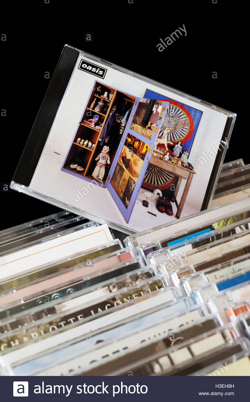 2006 Oasis compilation Stop The Clocks CD pulled out from among rows of other CD's - Stock Image
