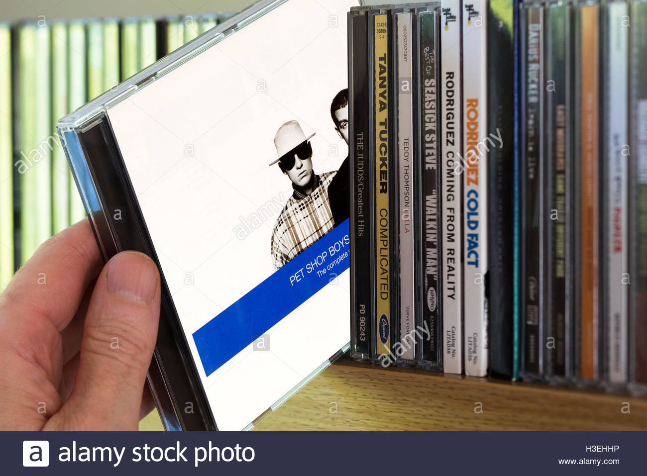 The Complete Singles Collection 1991 Pet Shop Boys-Discography CD being chosen from a shelf of other CD's - Stock Image