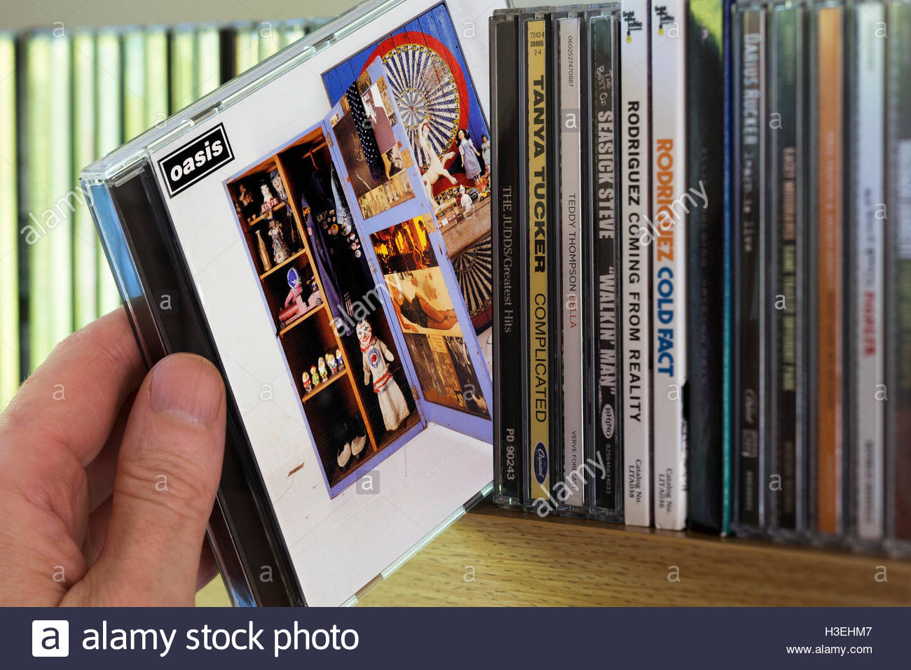2006 Oasis compilation Stop The Clocks CD being chosen from a shelf of other CD's - Stock Image