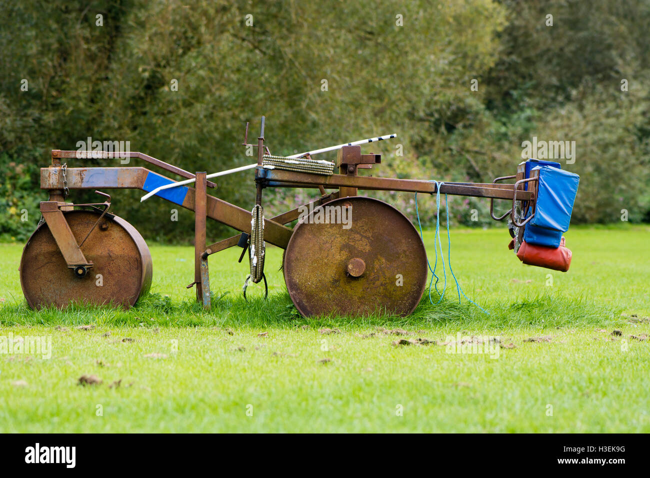 Rugby scrum machine in profile. Old and rusty Rugby scrummage training device on pitch near Bath, in Somerset, UK - Stock Image