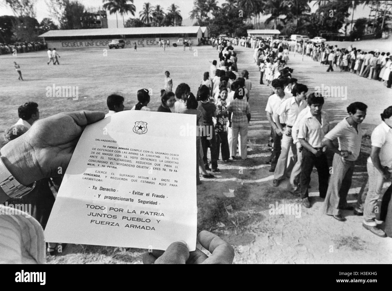 SAN SALVADOR, EL SALVADOR, 28th March 1982: Voter holds an army propaganda leaflet handed out to people wueuing - Stock Image