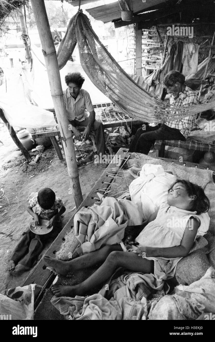 SAN VINCENTE, EL SALVADOR, March 1982:  a  child sleeps and adults pass the time in a camp for displaced people - Stock Image