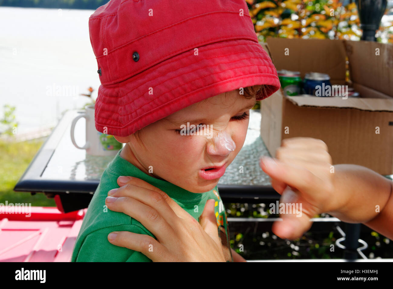A young boy (4 yrs old) reluctantly having suncream put on his face by his mum - Stock Image