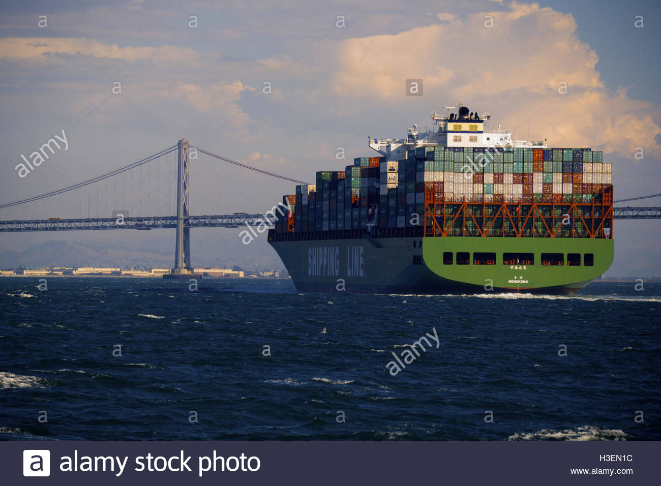 A Chinese cargo ship is stacked with shipping containers and is about to go under the San Francisco-Oakland Bay - Stock Image