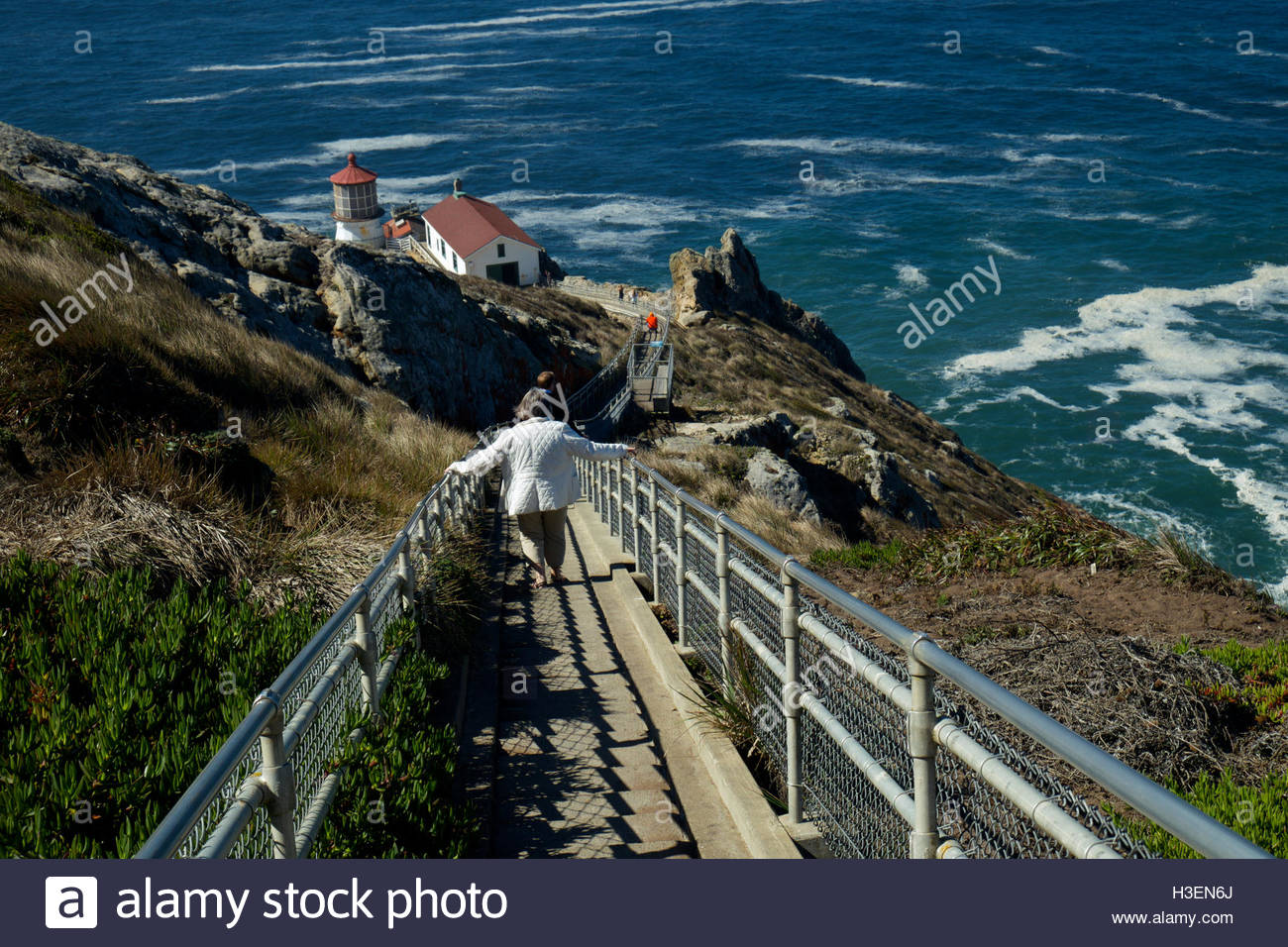 A woman holding a handrail steps down 308 steps to the Point Reyes Lighthouse in Point Reyes National Seashore, - Stock Image