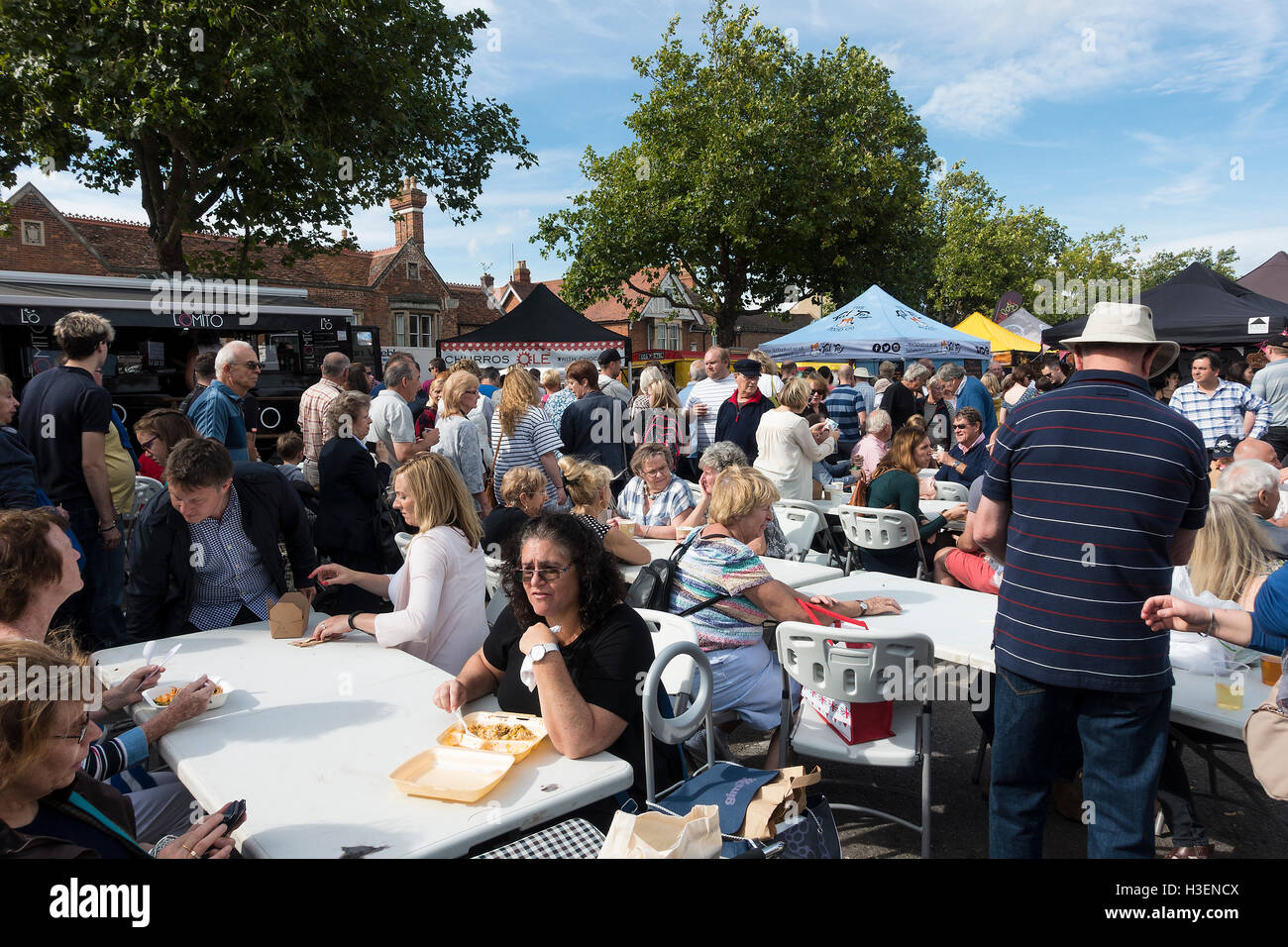 Colourful Stalls Surrounded by People at the Thame Festival of Food Oxfordshire England United Kingdom UK - Stock Image