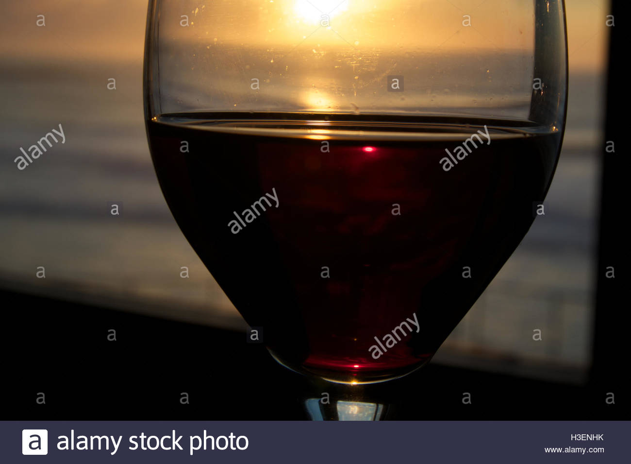 The setting sun over the Pacific Ocean shines through a window and a glass of red wine in Pacifica, California. - Stock Image