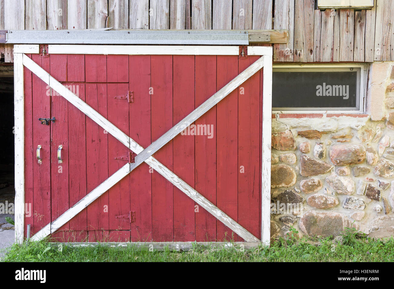 Partially open red barn door in a weathered barn. Traditional white ...