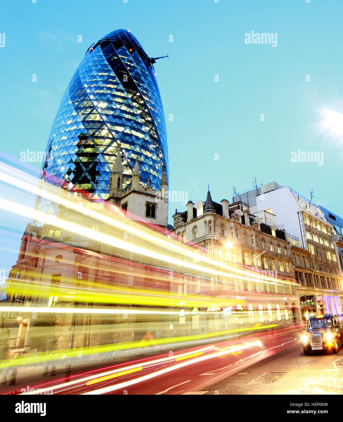 Red London bus passes 30 St Mary Axe,Gherkin,Swiss Re Building,City Of London,England at Dusk - Stock Image