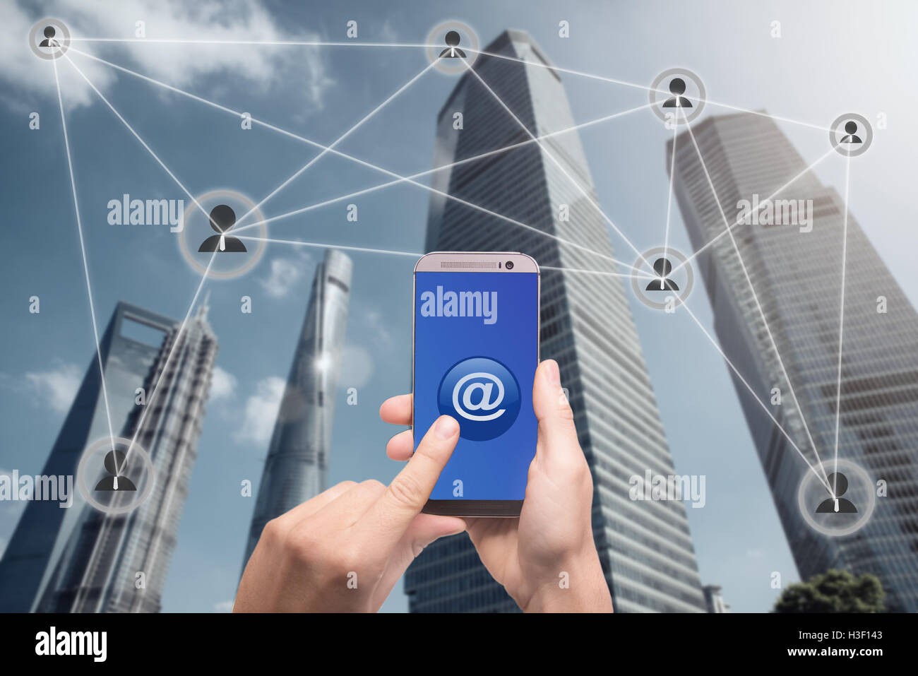 Hand holding smartphone and click on button with at sign linked with people icons. Email marketing, newsletter and - Stock Image