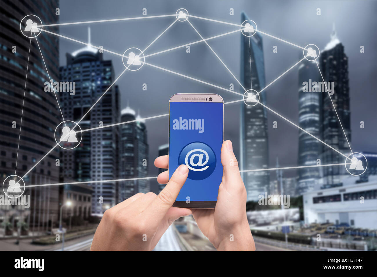 Hand holding smart phone and click on button with at sign linked with people icons. Email marketing, newsletter - Stock Image