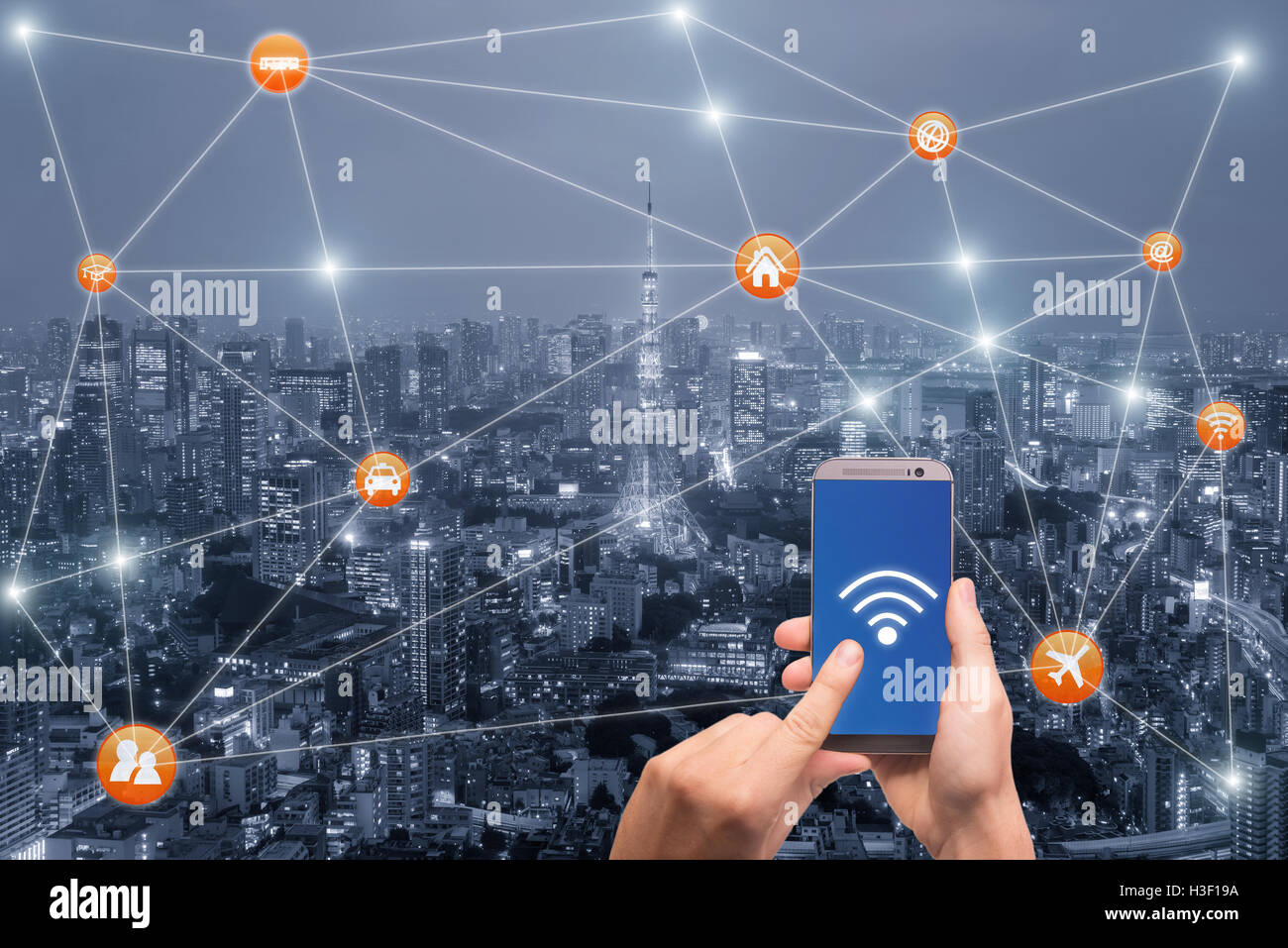 Hand holding smartphone with Tokyo city scape and wifi network connection. Smart city network connection concept - Stock Image