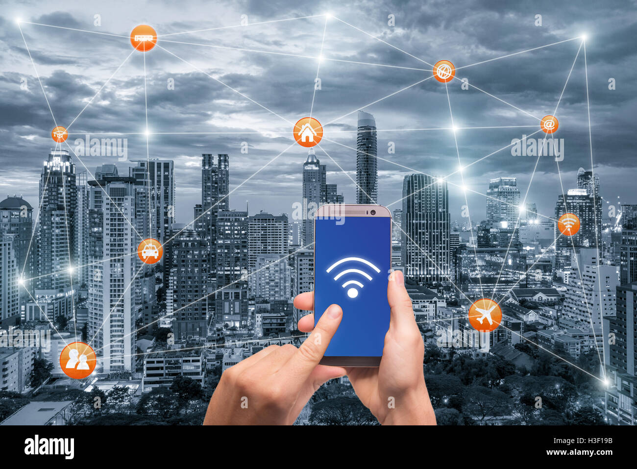Hand holding smartphone with bangkok city scape and wifi network connection. Smart city network connection concept - Stock Image