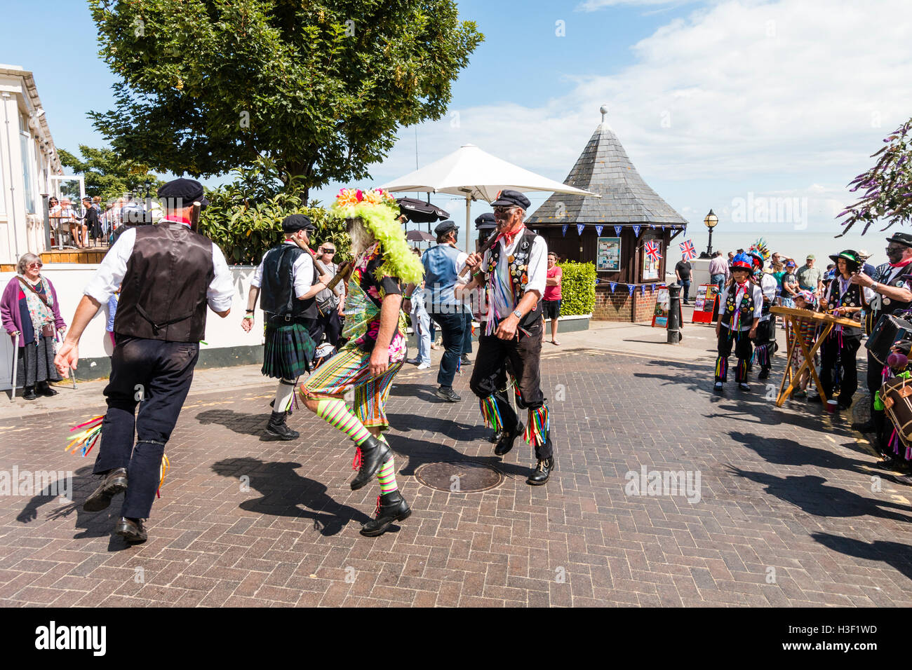 Traditional English folk dancers with blacked faces, Dead Horse Morris men dancing outdoors with their 'morris - Stock Image