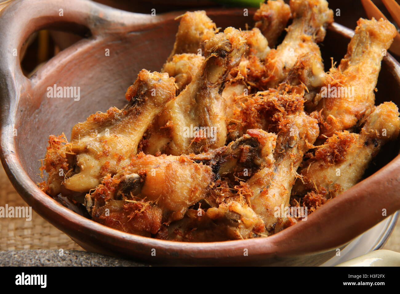 Fried chicken drummettes cooked with traditional Indonesian recipe. Served in an earthenware wok. - Stock Image