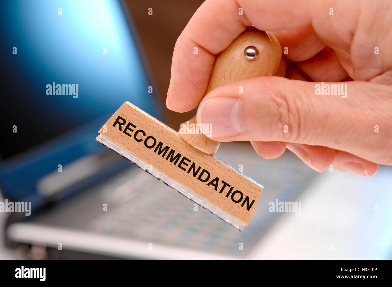 recommendation printed on rubber stamp in hand - Stock Image
