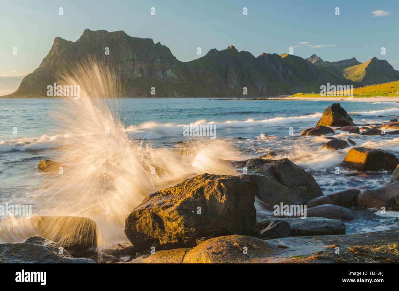 Rocks in evening light with warm light shining on them, waves coming to the shore and splashing on the rocks, Uttakleiv, Stock Photo