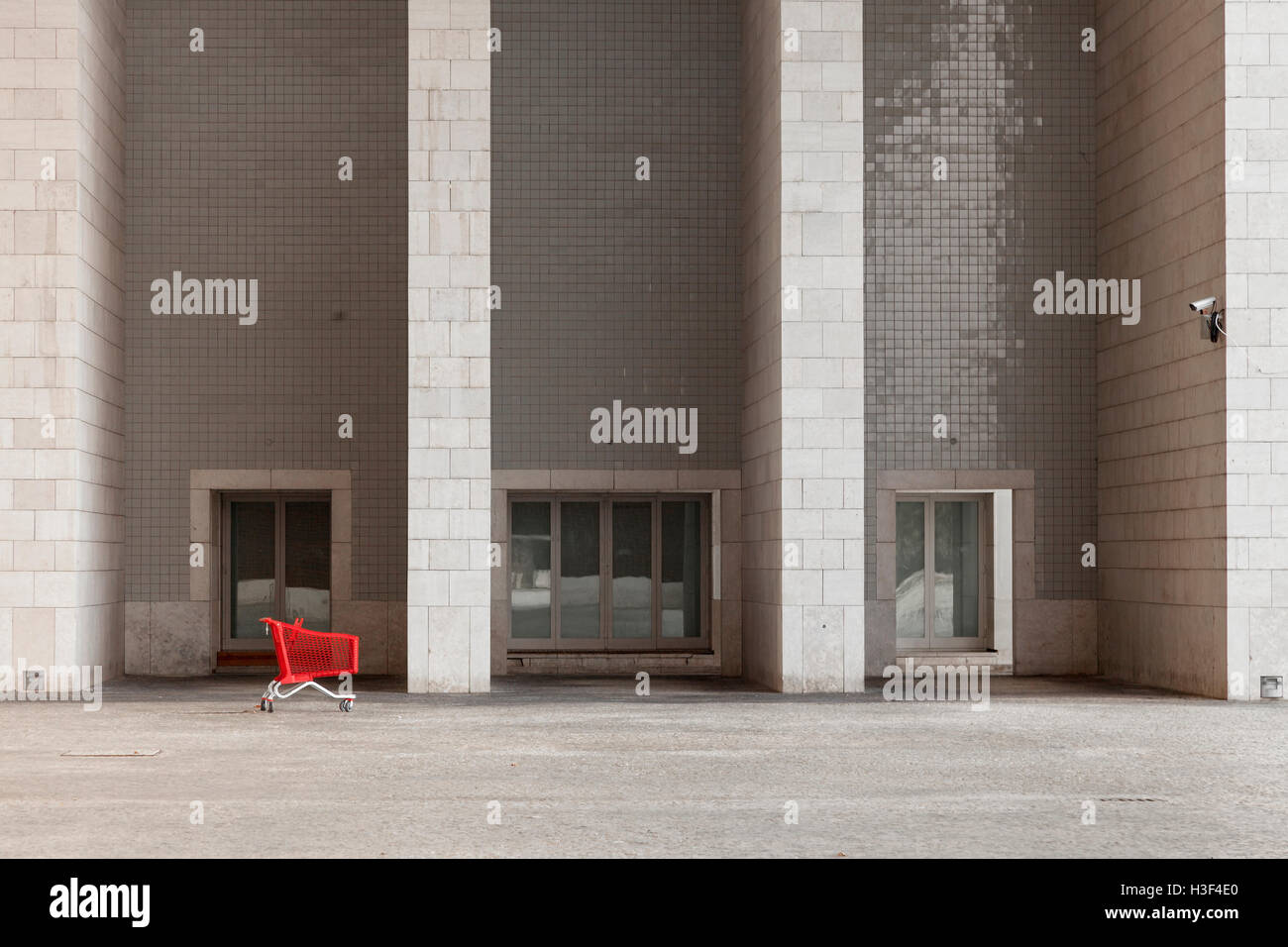 Red shopping cart in front of monumental building being observed by surveillance camera Stock Photo